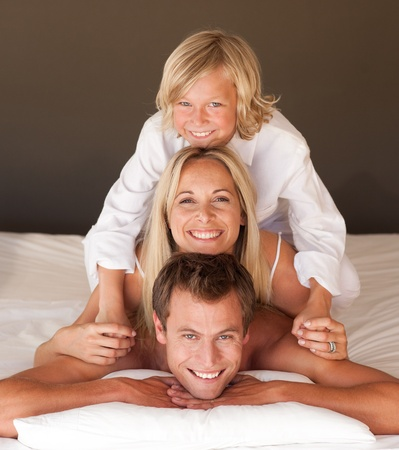Caucasian family having fun together lying on bed Stock Photo - 10129765