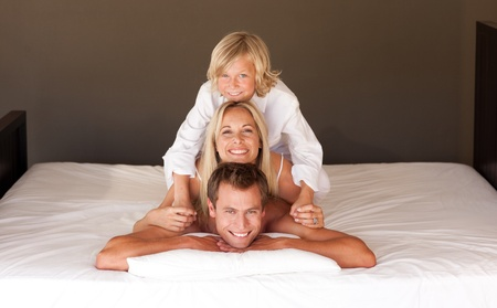 United family having fun together lying on bed Stock Photo - 10134327