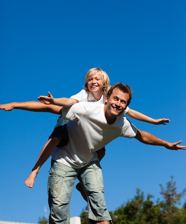 Attractive father with his son on his back outdoor photo
