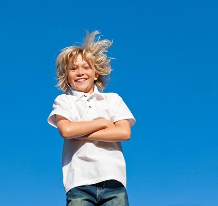 Joyful Kid with arms folded having fun outdoor  photo