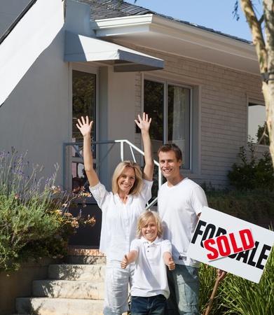 Vader, moeder en zoon in de voorkant van hun nieuwe huis Stockfoto