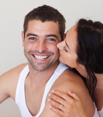 Portrait of girlfriend kissing her smiling boyfriend photo