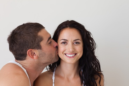 Attractive man kissing his smiling girlfriend photo