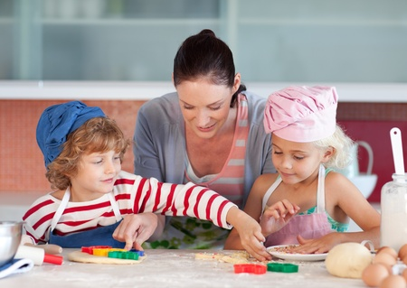 childrens food: Beautiful mother helping their chilldren baking Stock Photo