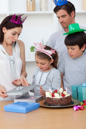 chirpy: Cute girl unpacking Birthday presents with her family Stock Photo
