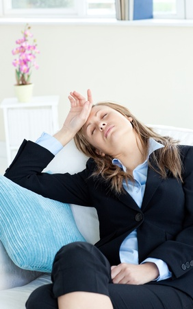 Stressed businesswoman slepping on a sofa Stock Photo - 10130845