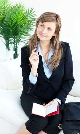 Thoughtful businesswoman taking notes photo