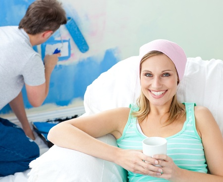 Relaxing smiling woman sitting on the sofa looking at the camera Stock Photo - 10130089