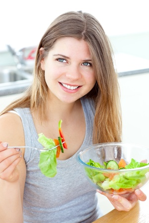 Smilling woman eating salad in the kitchen photo