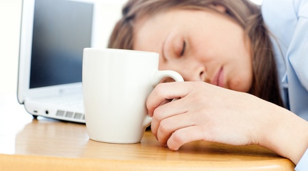 catnap: Slumbery woman sleeping on table in office Stock Photo