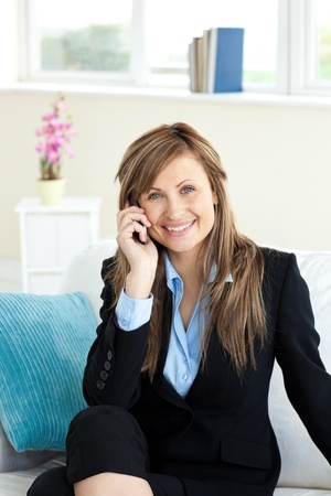 Positive businesswoman using a mobile phone i photo