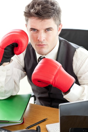 Angry businessman wearing boxing gloves in the office Stock Photo - 10133867