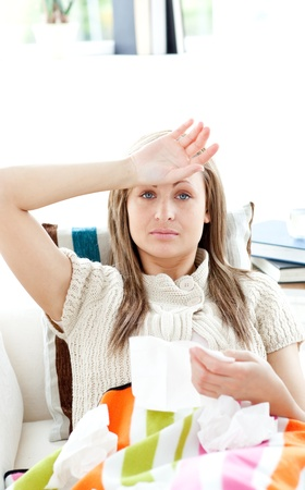 Portrait of a sick woman lying on a sofa holding tissue Stock Photo - 10130005