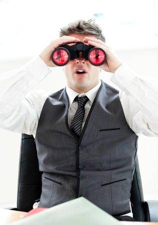 Impressed businessman looking through binoculars sitting in his office  photo