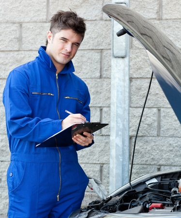 Attractive mechanic writing on a clipoard photo