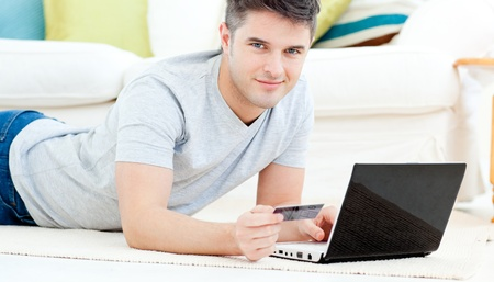 Smiling man lying on the floor with laptop holding a card photo
