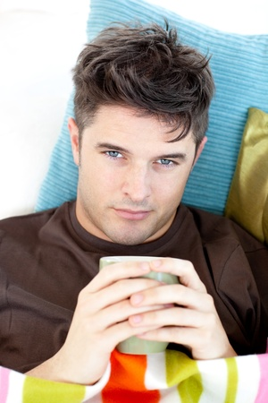 Sick man lying on a sofa holding a cup Stock Photo - 10134497
