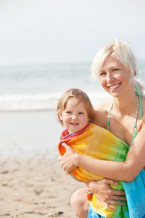A cheerful girl and her smiling mother at the beach photo