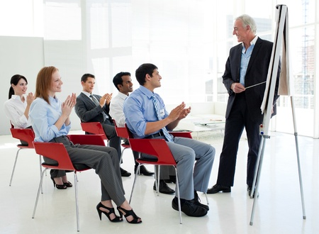 Business people applauding at the end of a conference photo