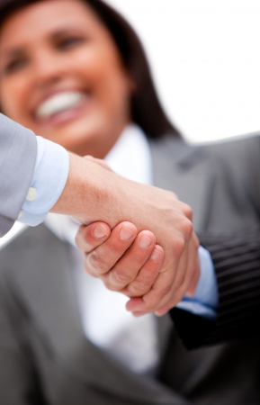 business transaction: Smiling businesswoman looking at her partners shaking hands