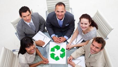 reciclaje papel: Gran �ngulo de sonriente equipo de negocios sosteniendo un s�mbolo de reciclaje