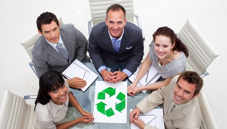 High angle of smiling business team holding a recycling symbol photo