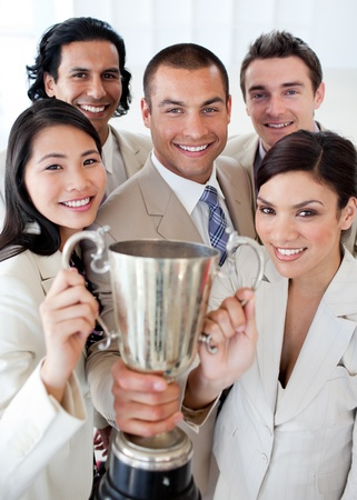 employees working: A successful business team holding a trophy