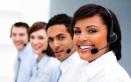 Ethnic businesswoman with headset on smiling at the camera  photo