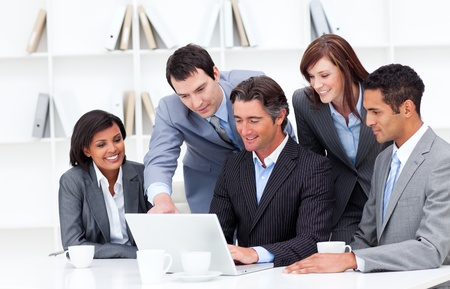 corporate culture: Multi-cultural business team looking at a laptop Stock Photo