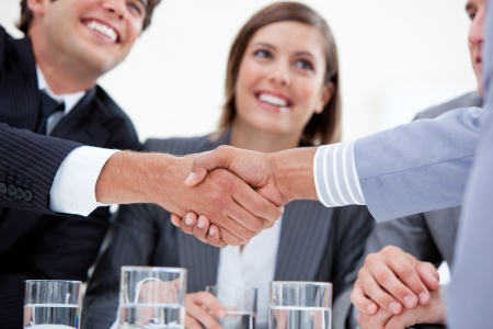 business deal: Smiling business people closing a deal