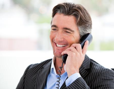 hablando por celular: Retrato de un hombre de negocios sonriente en el teléfono Foto de archivo