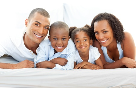 Happy family having fun lying down on bed Stock Photo - 10134364