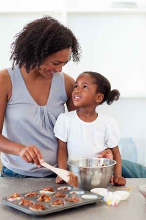 woman cooking: Happy mother helping her daughter cooking biscuits  Stock Photo