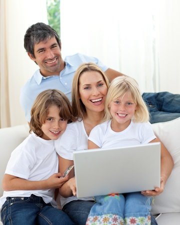 Cute children with their parents using a laptop  photo