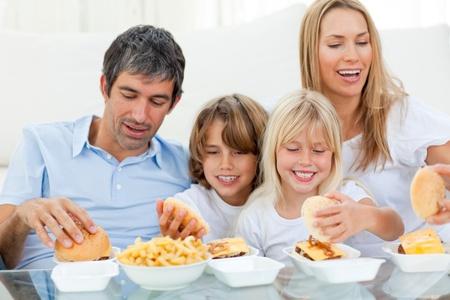 sharing food: Loving family eating hamburgers