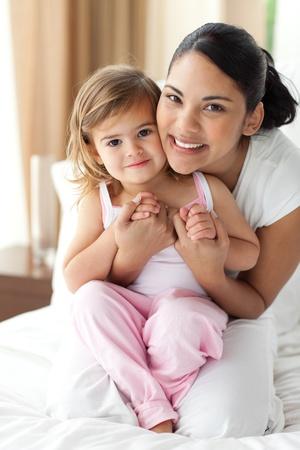 papa y mama: Madre sonriente abrazando a su ni�a  Foto de archivo