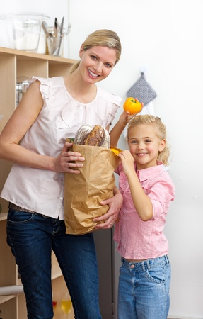 Happy mother and her Little girl unpacking grocery bag photo
