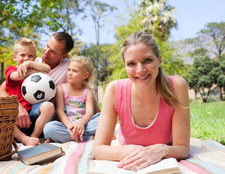 Smiling woman reading at a picnic with her family Stock Photo - 10134070