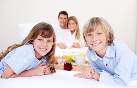Jolly family having breakfast sitting on bed photo