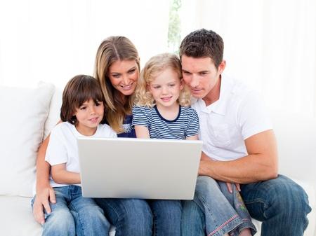 thinking machine: Retrato de una familia jolly utilizando una computadora port�til, sentado en el sof�
