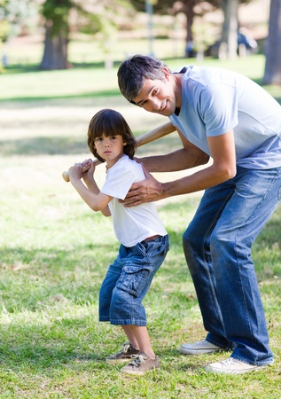 Smiling father teaching baseball to his son Stock Photo - 10133102