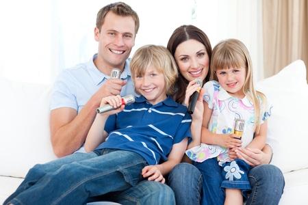 Lächelnde junge Familie, die ein Karaoke singen