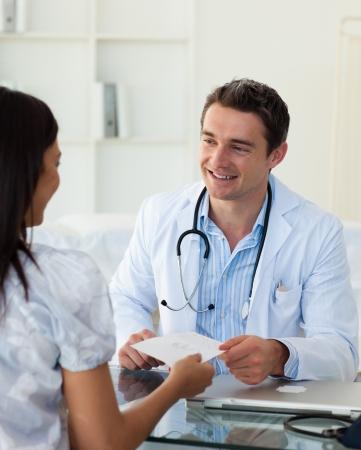 arzt gespr�ch: Smiling Doctor geben ein Rezept, um seine Patientin