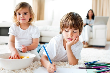 Serious little boy drawing and his sister eating chips photo