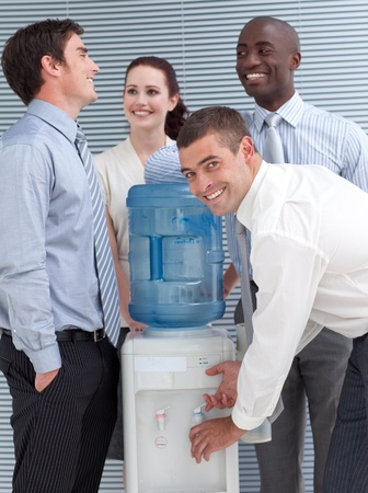 man drinking water: Business colleagues talking around water cooler