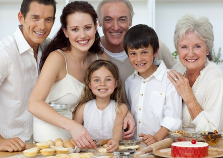 Portrait of parents, grandparents and children baking in the kitchen