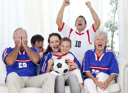 Familie kijken naar een voetbalwedstrijd in televisie Stockfoto