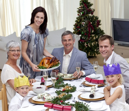 Family celebrating Christmas dinner with turkey photo