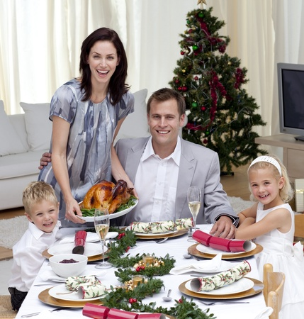 Parents and children celebrating Christmas dinner with turkey photo