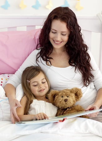 Happy mother and daughter reading in bed photo